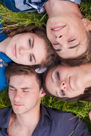 Four happy teenage friends boys and girls lying together on green grass outdoors photo