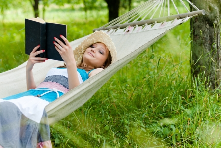 Happy young woman reading in hammock in green park outdoors Stockfoto