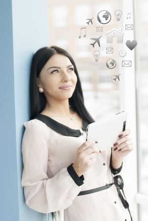 Portrait of a happy smiling young business woman using tablet PC while standing relaxed near window at her office photo