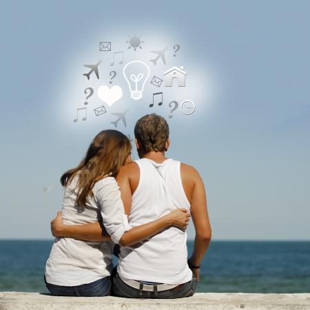 Young happy couple at sea coast sitting hugging idea symbols above them photo