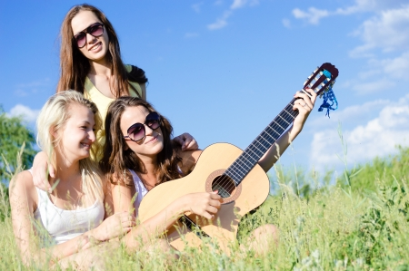 Three happy teen girls singing and playing guitar against blue sky on bright summer day photo