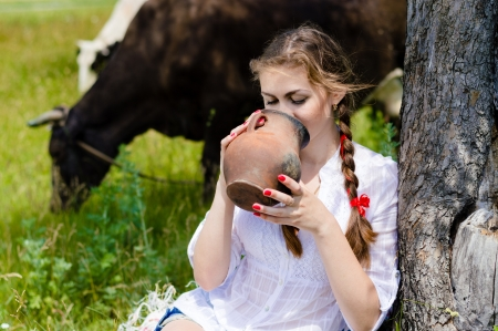 Young happy woman drinking fresh milk near cows in countryside on summer day photo