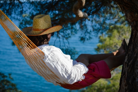 Lazy time  Man in hat in a hammock on a summer day Stockfoto