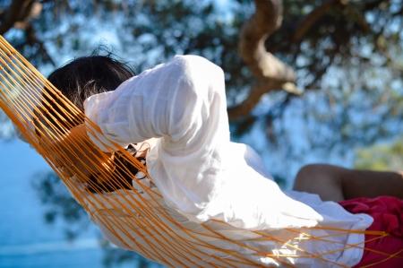 unworried: Lazy time  Man in hat in a hammock on pine tree in Crimea a summer day