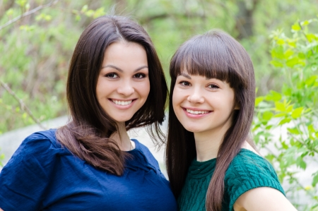 Two sisters or girl friends smiling, laughing and hug outdoors in spring or summer photo