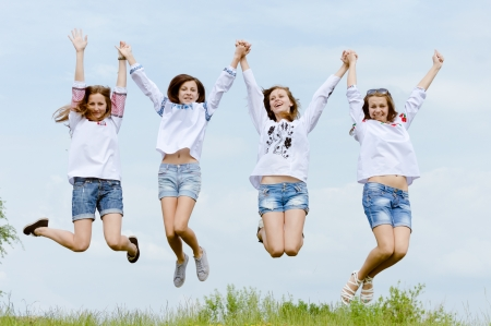 Four happy teenage friends girls jumping high in blue sky photo