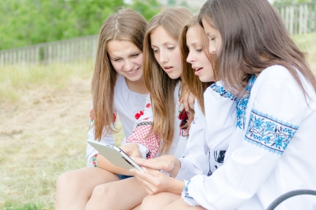 Group of happy teen girl friends looking on tablet pc while sitting on bench on summer day photo