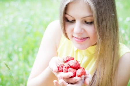 Young happy teen girl eating strawberry from huge bowl on summer day outdoors photo