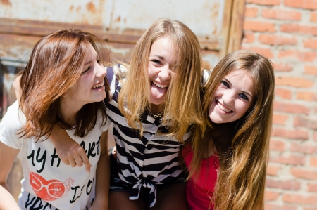 Three young happy teenage girl friends have fun in city outdoors photo