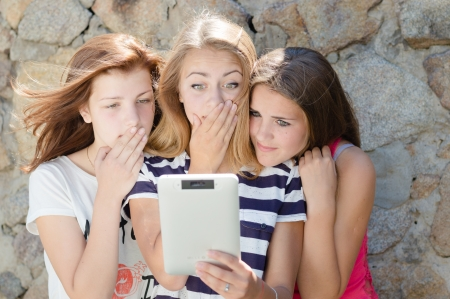 Three amazed teen girl friends looking on tablet pc on summer day photo