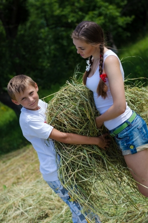 Teenage sister and little brother holding velour grass or hay photo