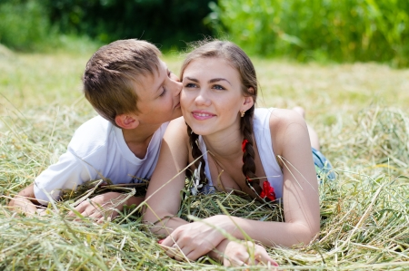 Teenage sister and little brother lying on hay on summer day outdoors photo