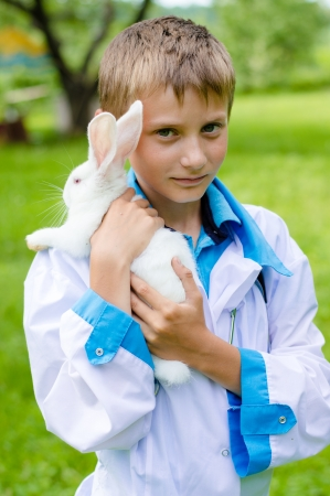 young happy boy in doctor cloth embracing little rabbit outdoors on summer day photo
