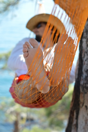 Lazy time. Man in hat in a hammock on pine tree in Crimea a summer day photo