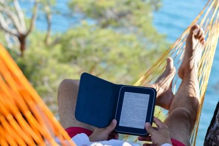Man resting in orenga hammock on seashore and reading ebook