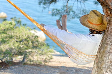 unworried: Lazy time. Man in hat in a hammock on pine tree in Crimea a summer day Stock Photo