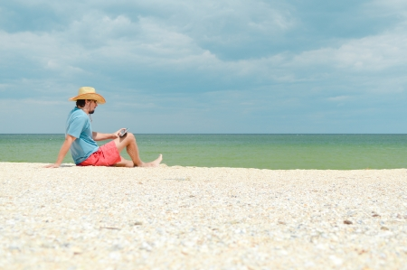 Young man sitting at seaside on sandy beach with tablet computer and resting photo