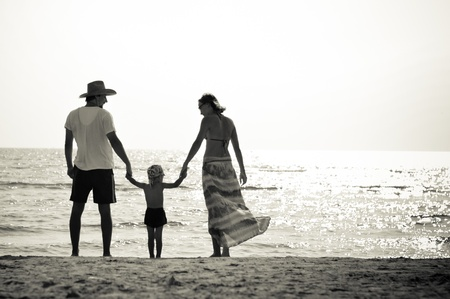 Happy family mother father and little son on sandy beach\ having fun
