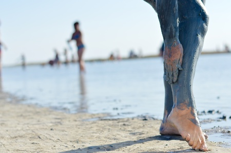 Mature woman applying mineral blue mud on legs at Sivash lake photo