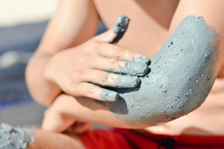 Young man om sandy beach applying mineral blue mud on elbow closeup