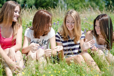 cute girlfriends: Four happy teen girls sitting on green lawn and sharing secrets Stock Photo