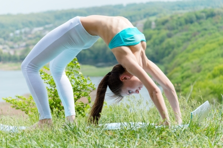Happy young woman doing yoga on green river bank photo