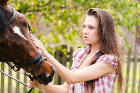 Beautiful young woman holding horse on summer day photo