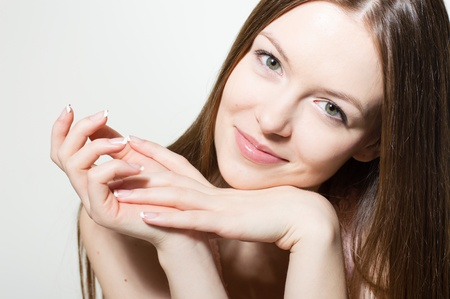 Portrait of beautiful young woman face  Perfect skin, fresh manicure photo