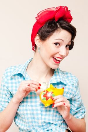 spendthrift: Retro pinup woman put money dollar note to porcelain mouse bank Stock Photo