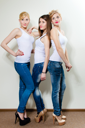 women jeans: Three beautiful women in blue jeans and high heels, studio shot Stock Photo