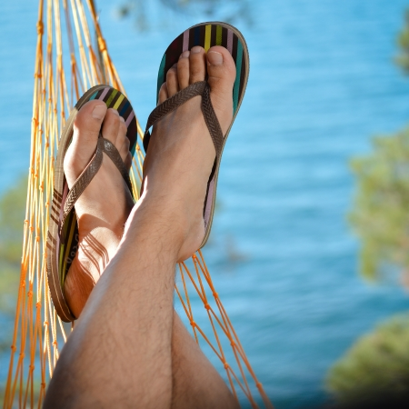beach feet: Young man relaxing on hammock on beach