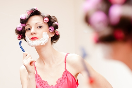 Beautiful funny young woman shaving with foam & razor her face Stock Photo