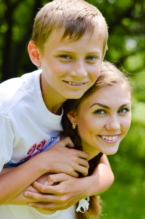 Teenage sisrer and little brother hugging outdoors on summer day photo