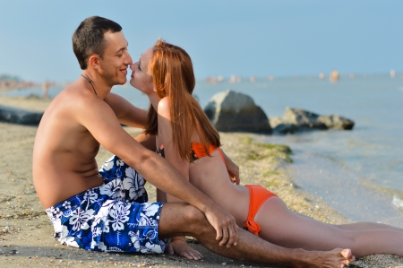 Young happy couple together on sandy beach embracing photo
