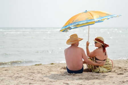 Happy mature couple sitting at seashore on sandy beach back to back photo