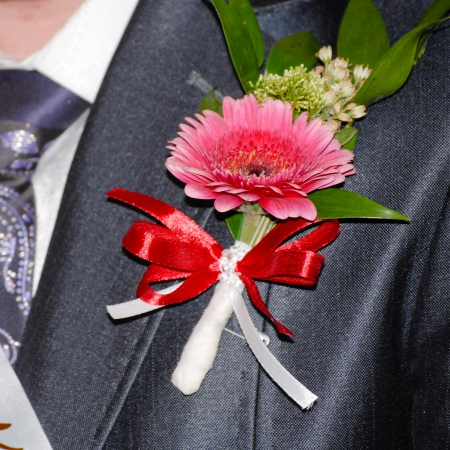 Beautiful gerbera and rose boutonniere on groom suit or tuxedo photo