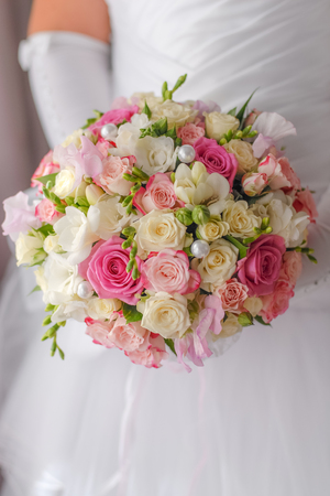 Wedding roses bouquet  in bride hands closeup photo