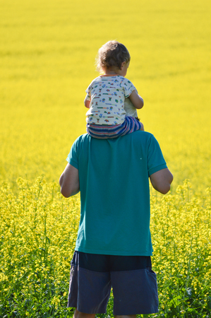 Father and little son looking on rapeseed field on summer day photo