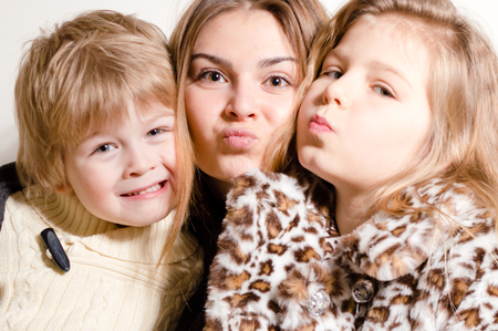 Three happy brother and sisters hug and kiss photo