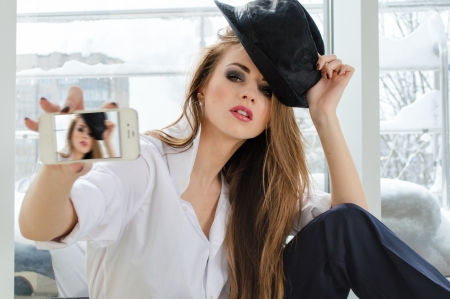 Beautiful young woman taking picture of herself on mobile