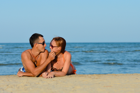 Young happy couple man and woman lying on sandy beach photo