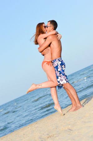 Young happy couple together on sandy beach embracing Stock Photo - 23331128