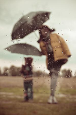 Mother and son under umbrella silhouette through wet window photo