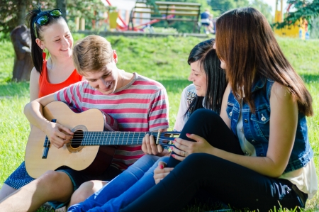 Group of happy teen friends playing guitar in green summer park photo