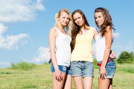 Three happy teen girls sitting on green grass and embracing against blue sky on bright summer day