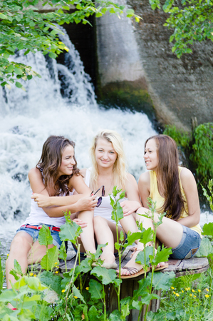 Three happy teen girls talking at waterfall on summer day outdoor photo