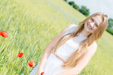 Young beautiful woman walking in green wheat field on summer day photo
