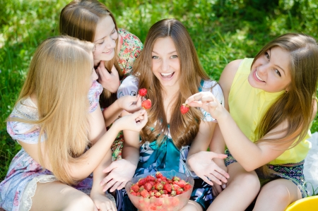 Four happy teenage girls eating strawberry and having fun outdoors on summer day photo