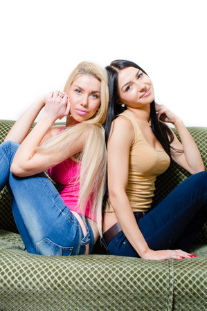 sisters sexy: Portrait of two beautiful sexy girlfriends or sisters sitting together on sofa & white background