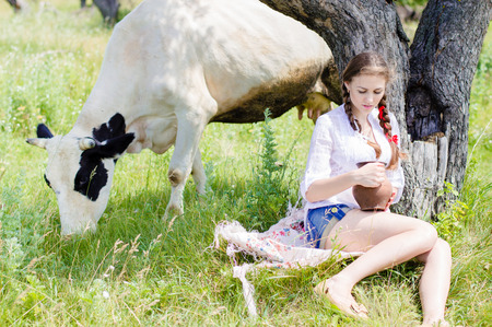 Young happy woman sitting tired near cows in countryside on summer day photo